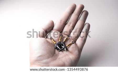 """Finger holding mini Japanese traditional ninja warrior weapon called kunai with kanji writing of """"shinobu"""", meaning to endure or conceal. Concept of endurance. Isolated on empty background. Copy space"""