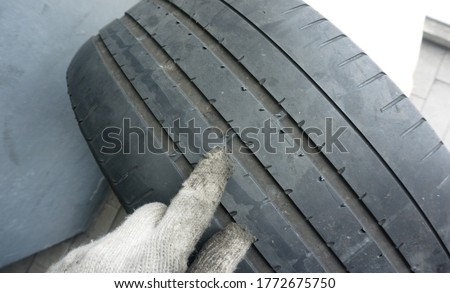 Finger in glove of mechanic pointing at tyre tread wear indicators, Tread wear indicators, built into the main tread grooves, show the tread depth. Foto stock ©