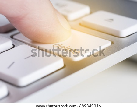 Finger is pressing delete key of a aluminum white computer keyboard