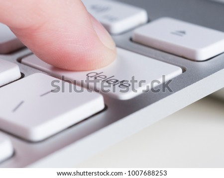 Finger is pressing delete key of computer keyboard