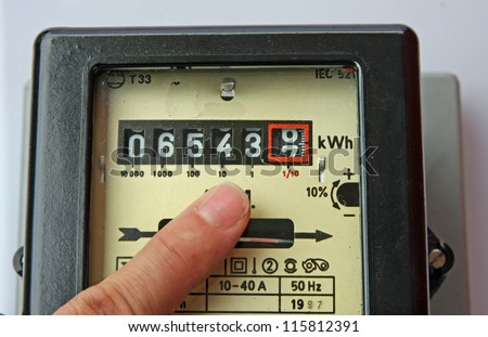 finger of a man indicating the figures in an electric energy meter