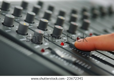 Finger on mixing desk