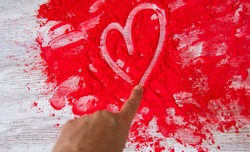 Finger painting a heart on red powder. Love concept