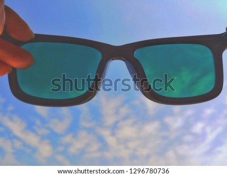 finger pick up black sunglasses held up to look at the bright blue sky. Giving the atmosphere of summer. Brightness and hot concept. #1296780736
