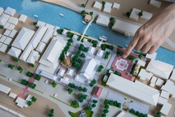 finger pointed to mass model of landscape design or garden design or landscape architecture in waterfront temple area with group of buildings and trees in community,  bird's eye view, selective focus
