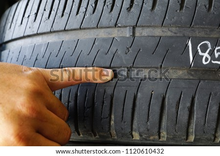 Finger pointing at tyre treadwear indicator / Tyre check and replacement for safety concept