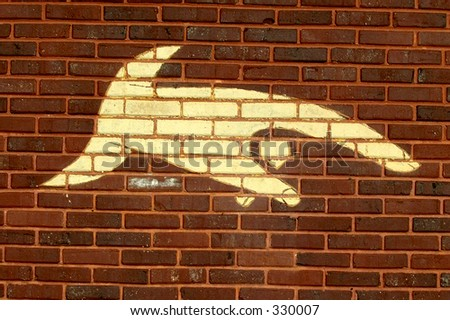 Finger pointing down painted on a brick wall. - stock photo