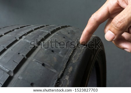 Finger pointing to damage on tire tread. Tire tread problems by tire pressure improper, Wheel alignment