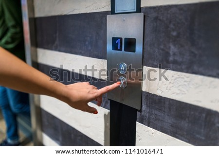 Finger presses the elevator button. Female finger pushing elevator button. Hand press a button of elevator inside the building for upper high level floor, Close up shot and focus on button