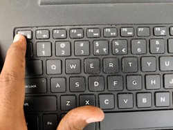 Finger pressing a Esc (Escape) button on the laptop keyboard. Selective focus