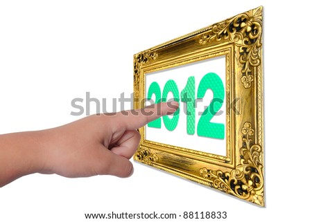 Finger pressing a touchscreen button to 2012 on gold frame