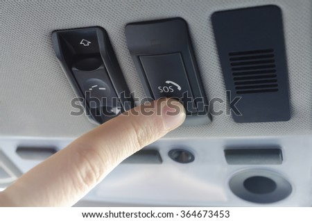 Finger pressing emergency sos button to contact with call center to ask for help after car accident