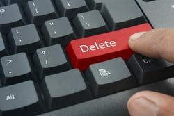 finger pressing red delete keyboard button