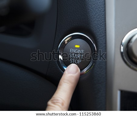 finger pressing the Engine start stop button of a car - stock photo