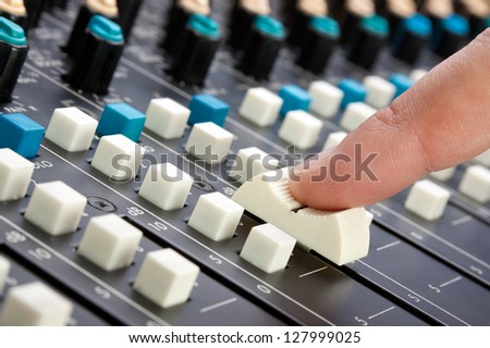 Finger pushing a mixing desk slider; shallow depth of field