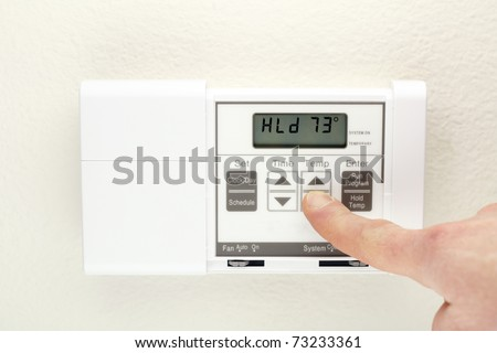 Finger pushing control buttons on heating and cooling digital wall panel display.