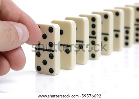 Finger pushing dominoes in a row causing a chain reaction