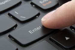 Finger pushing enter button on black computer keyboard; Macro photo
