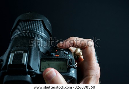 Finger pushing shutter button on a digital camera on a black background.