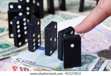 Finger pushing standing dominoes on pound, euro and dollar bank notes illustrating banking crisis