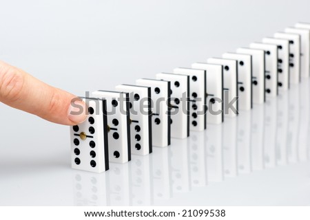 Finger ready to start domino chain reaction