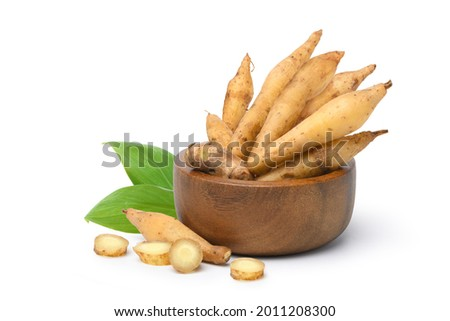 Finger root in wooden bowl with slices isolated on white background.