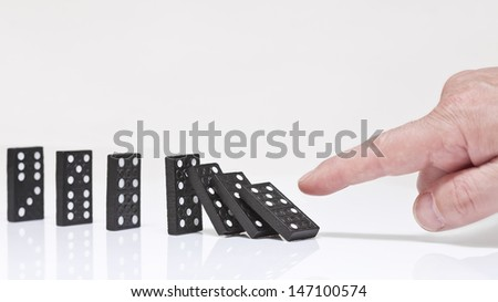 Finger toppling dominoes. Domino effect.