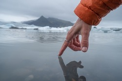 Finger touches surface of glacier lagoon People nature concept. Shot in Iceland, Europe