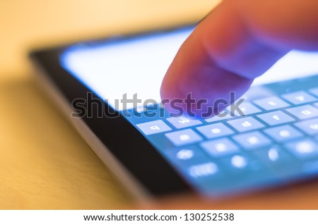 finger touching w on virtual keyboard on tablet-pc