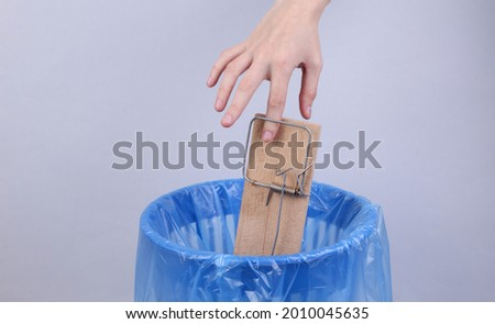 Finger trapped in a mousetrap on the background of trash can Photo stock ©
