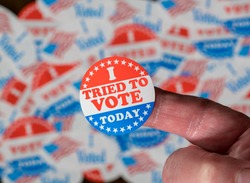 Finger with I Voted button in front of voting stickers given to US voters in Presidential election to illustrate vote suppression or rejections