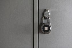 fingerprint padlock is locked and hanging on cell of storage locker in hostel