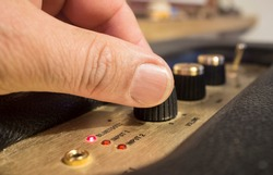 Fingers adjusts fine-tune controls of retro style  speaker. Selective focus