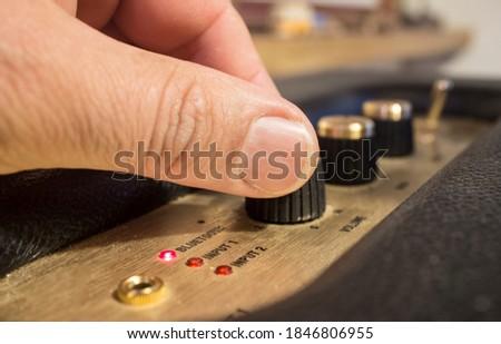 Fingers adjusts fine-tune controls of retro style  speaker. Selective focus Photo stock ©
