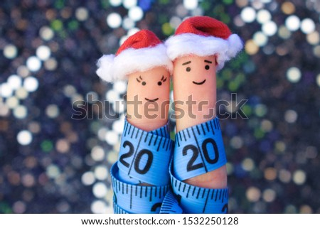 Fingers art of couple celebrates Christmas. Concept of man and woman laughing in New Year hats. Measuring tape is written 2020. Toned image.