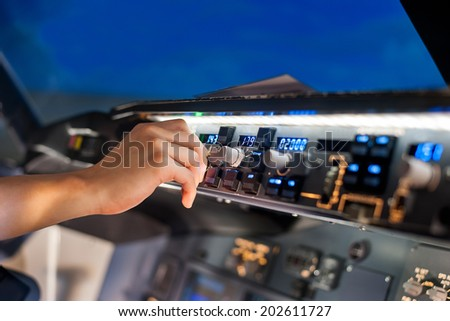 fingers controls the switch control panel in a plane cockpit