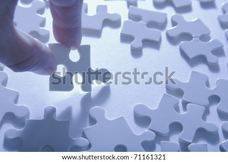 Fingers holding a jigsaw puzzle piece above others.