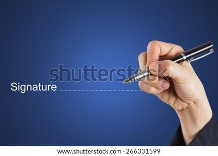 Fingers holding pen writing signature