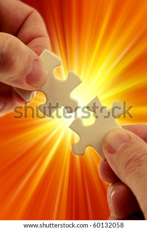 Fingers holding two puzzle pieces over bright background