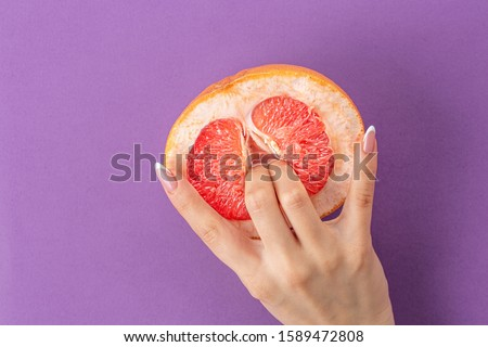 fingers in grapefruit on purple background. Sex concept. sexy fruit composition. Vagina symbol.