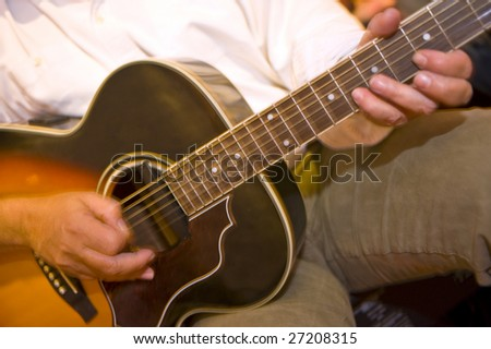 Fingers in motion on on the soundboard of an acoustic guitar