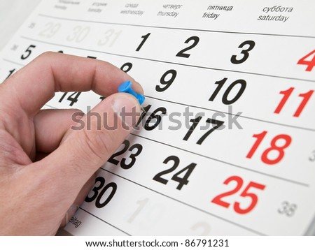 Fingers making marks on the calendar page