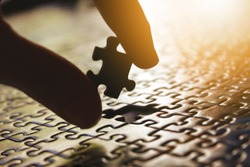 Fingers of a white man putting the last piece of a puzzle. Man building a puzzle. Metaphor and symbol of integration, teamwork, effort