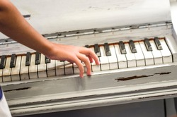 fingers of a young student's hands play excellent music from the keys of the old piano
