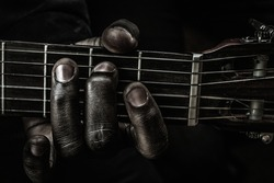 Fingers of blues: Fingers and strings in a close up, playing the guitar, making a tune.