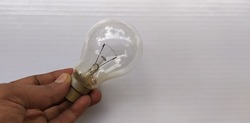 fingers of hand holding one single vintage Thomas Alva Edison style type old model incandescent transparent glass tungsten heat light bulb with white table background and copy space. Closeup side view