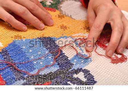 Fingers of young women, cross embroidery.