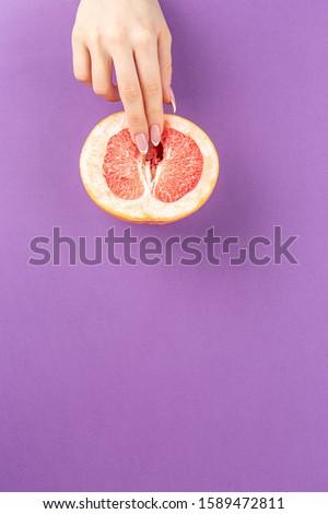 fingers on grapefruit on purple background. woman masturbation concept. sexy fruit composition. Vagina symbol.