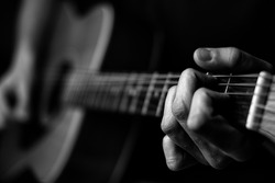 Fingers on guitar strings in black and white