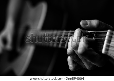 Fingers on guitar strings in black and white #366894554